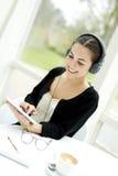 Vrouw die aan Hoofdtelefoons luistert Stock Afbeeldingen