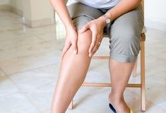 Vrouw die aan kniepijn lijdt Royalty-vrije Stock Foto's