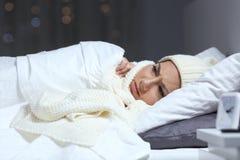 Vrouw die aan koude in een bed in de winter lijden stock foto