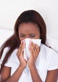 Vrouw die aan koude thuis lijden Stock Foto