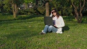 Vrouw die aan laptop in aard werken Het meisje in het park zit op het gras met de computer Jonge vrouw in zonnebrilworki stock videobeelden
