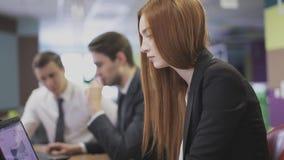 Vrouw die aan laptop in bureau werkt stock footage