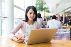 Vrouw die aan laptop computer werken en cellphone gebruiken stock foto