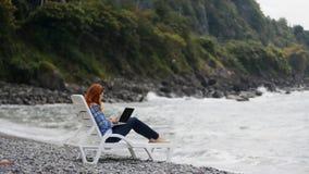 Vrouw die aan laptop dichtbij het overzees werken stock footage