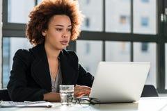 Vrouw die aan laptop in het bureau werkt stock afbeeldingen