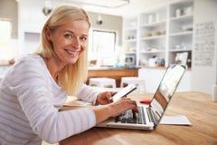 Vrouw die aan laptop thuis werkt Stock Foto