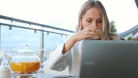 Vrouw die aan moderne laptop en het drinken thee in koffie werken stock videobeelden