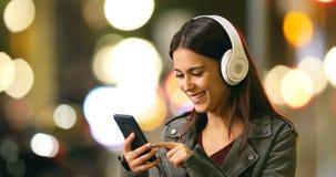 Vrouw die aan muziek in de nacht luisteren stock videobeelden