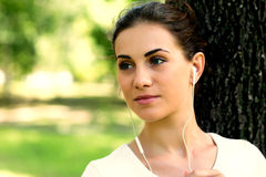 Vrouw die aan muziek luisteren die met hoofdtelefoons stromen Royalty-vrije Stock Afbeelding