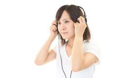 Vrouw die aan muziek luistert Stock Foto