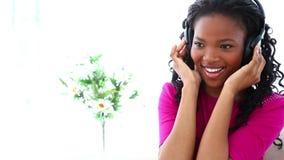 Vrouw die aan muziek met hoofdtelefoons luistert stock footage