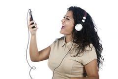 Vrouw die aan muziek met mobiele telefoon luisteren Stock Afbeeldingen