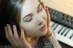 vrouw die aan muziek op een synthesizerachtergrond luisteren stock foto