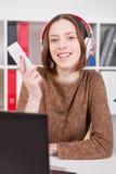 Vrouw die aan muziek op het kantoor luisteren Gebruik app aan uw smartphone Royalty-vrije Stock Afbeeldingen