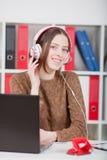 Vrouw die aan muziek op het kantoor luisteren Hij onderzoekt de camera Royalty-vrije Stock Foto's
