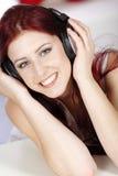 Vrouw die aan muziek op hoofdtelefoons luistert Stock Fotografie