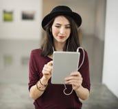 Vrouw die aan muziek van haar tablet luisteren stock afbeelding