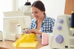 Vrouw die aan naaimachine werken Stock Afbeelding