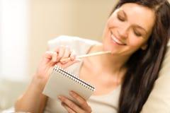 Vrouw die aan notitieboekje schrijven Stock Foto's
