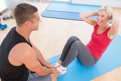 Vrouw die aan oefeningsmat werken met haar trainer Stock Foto's