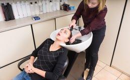 Vrouw die aan Stilist babbelen terwijl het Hebben van Gewassen Haar royalty-vrije stock fotografie