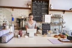 Vrouw die aan tot bij de teller van een koffiewinkel werken royalty-vrije stock afbeelding