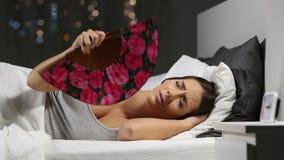 Vrouw die aan zonnesteek in de nacht in het bed lijden stock video