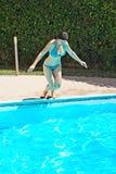 Vrouw die aan zwembad springt Royalty-vrije Stock Foto's