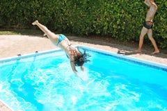 Vrouw die aan zwembad springt Stock Afbeelding