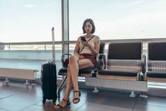 Vrouw die in aankomstzaal rust die op een overdracht bij luchthaven wacht royalty-vrije stock foto's