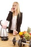 Vrouw die aardbei eet door mixer royalty-vrije stock afbeeldingen