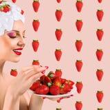 Vrouw die Aardbei eten Stock Afbeeldingen