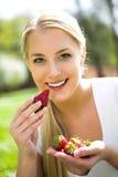 Vrouw die aardbeien eet Stock Afbeelding