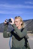 Vrouw die aardfoto in zand neemt Stock Afbeelding