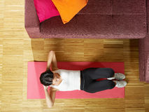 Vrouw die abs oefening thuis doet stock afbeelding