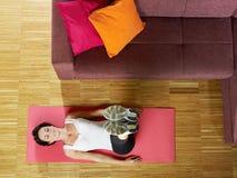 Vrouw die abs oefening thuis doet stock foto