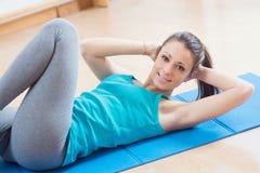 Vrouw die abs training doen bij gymnastiek stock afbeeldingen