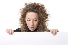 Vrouw die achter leeg aanplakbord gluurt royalty-vrije stock foto
