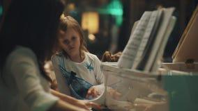 Vrouw die actief de piano spelen, die dichtbij meisje zitten herhaalt vingerbeweging stock video