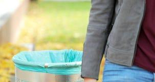 Vrouw die afval werpen in bak in een park stock videobeelden