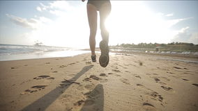 Vrouw die alleen bij mooie zonsondergang op het strand lopen Langzame Motie stock videobeelden