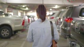 Vrouw die alleen in parkeerterrein lopen stock video