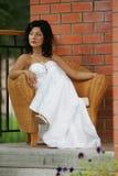 Vrouw die als voorzitter in huwelijkskleding wordt gezeten Stock Afbeeldingen