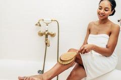 Vrouw die anti-anti-cellulite droge borstel gebruiken stock fotografie