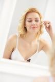 Vrouw die anti-veroudert vochtinbrengende crème toepassen Stock Foto's