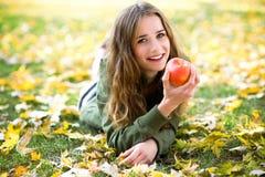 Vrouw die appel in openlucht in de herfst eet Stock Afbeeldingen