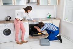 Vrouw die Arbeider bekijken die Oven herstellen stock fotografie