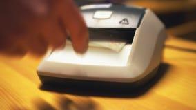 Vrouw die automatische vervalste gelddetector met behulp van stock video