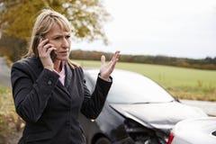 Vrouw die Autoongeval bij de Landweg roepen te melden stock fotografie