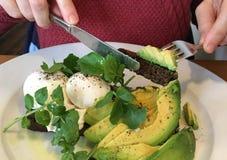 Vrouw die avocado op toost voor brunch eten stock fotografie